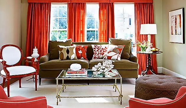 Эффектное сочетание красных штор и темно-зеленого дивана