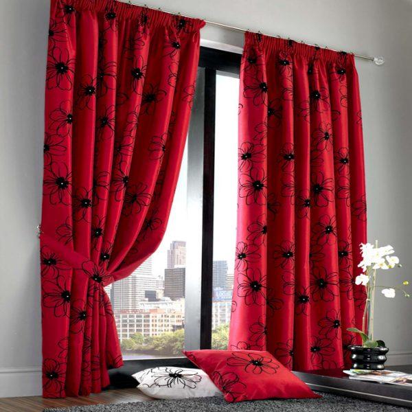 Красные шторы с черными цветами гармонично впишутся в интерьер гостиной в деревенском стиле
