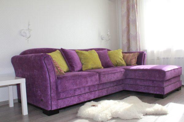 Лавандовый диван и белый ковер на полу