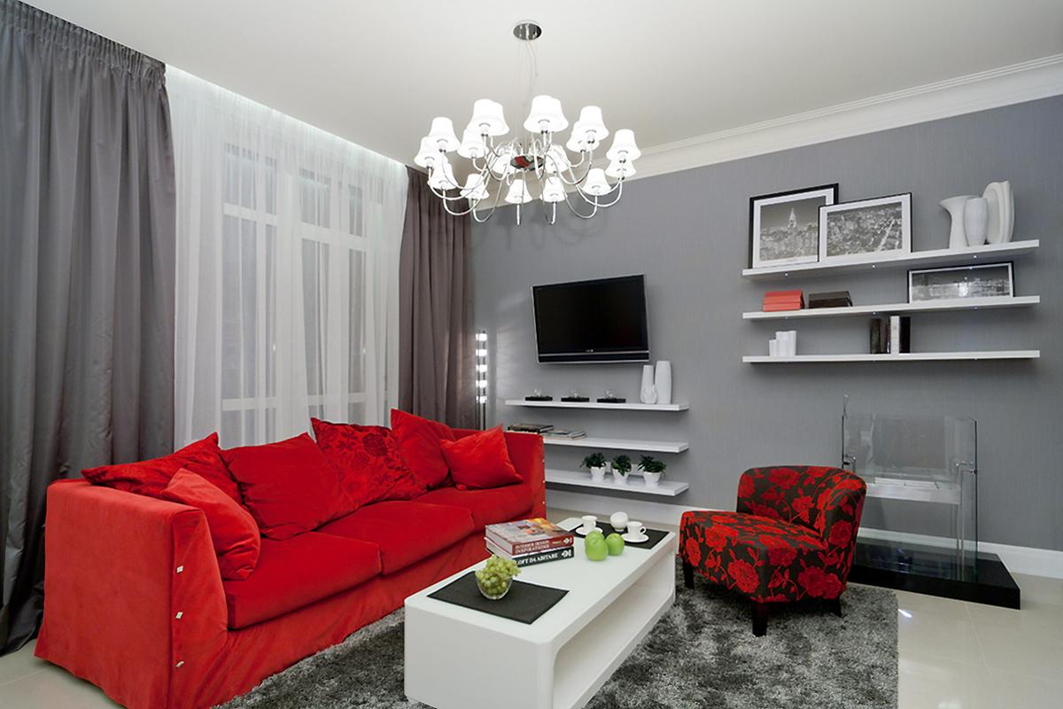 Серая гостиная с красным диваном