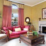 Небольшой диван малинового цвета в гостиной