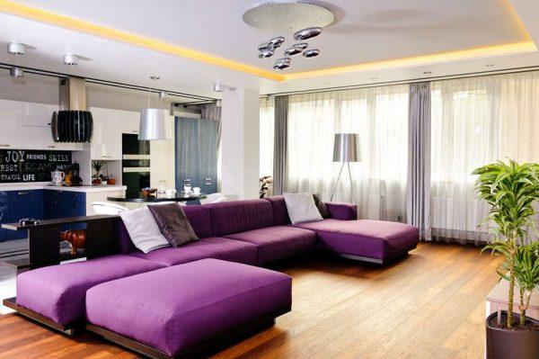 Большой фиолетовый диван в совмещенной гостиной-кухне